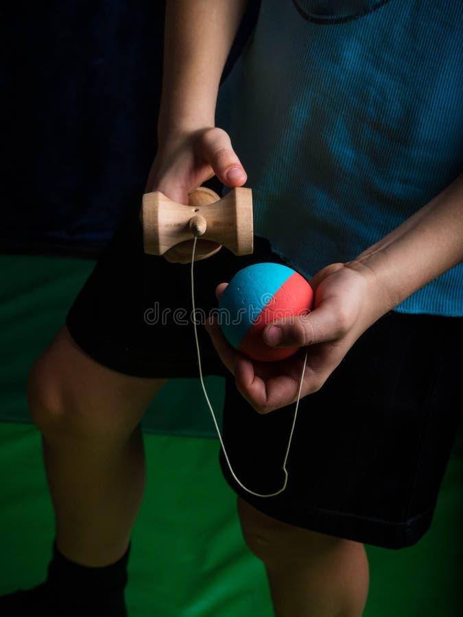 Классическое японское kendama игры, руки мальчика играя kendama стоковая фотография