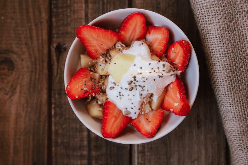 Клубники с семенами подсолнуха chia семян тыквы семян йогурта и яблоко в белом шаре на деревянном столе стоковое изображение