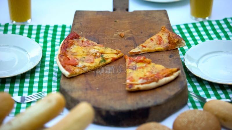 Куски пиццы лежа на деревянной доске в ресторане, вкусной еде для большой компании стоковое фото rf