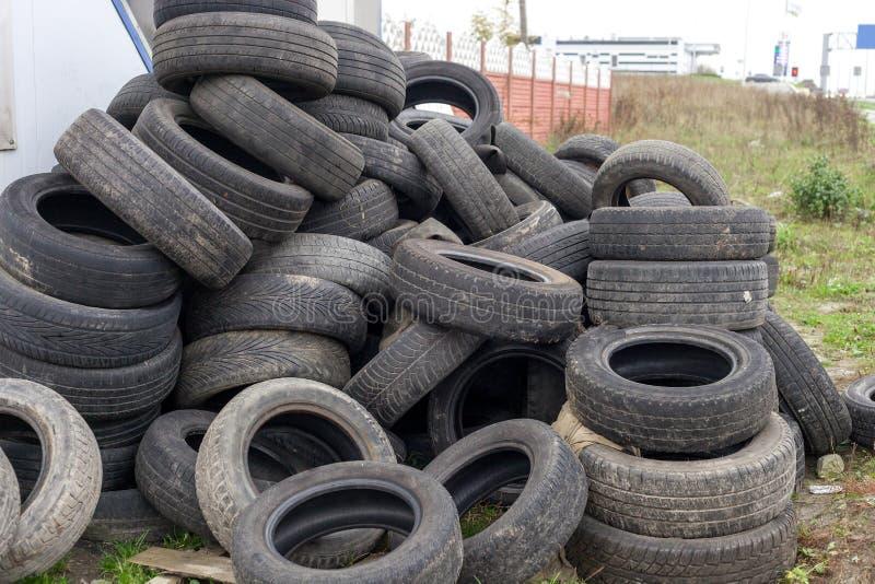Куча старых используемых черных автошин автомобиля на junkyard стоковые фотографии rf