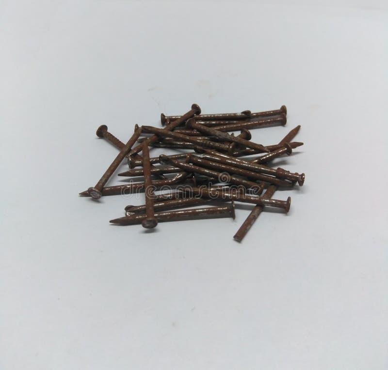 Куча ржавых ногтей на белой предпосылке стоковые фотографии rf