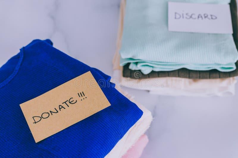 Кучи футболок и одежд будучи сортированными в держат сбрасывание и дарят категории стоковые фотографии rf