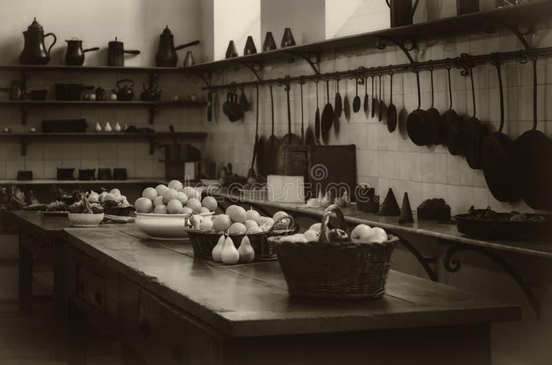 Кухня античного столетия XIX старая с инструментами, лотками, баками и пищевыми ингредиентами стоковые изображения rf