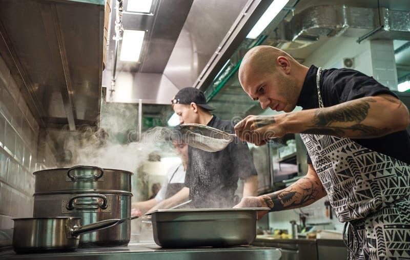 Кухня ресторана Профессиональный шеф-повар в рисберме, с татуировками на его оружиях просеивает муку пока варящ с его 2 стоковая фотография rf