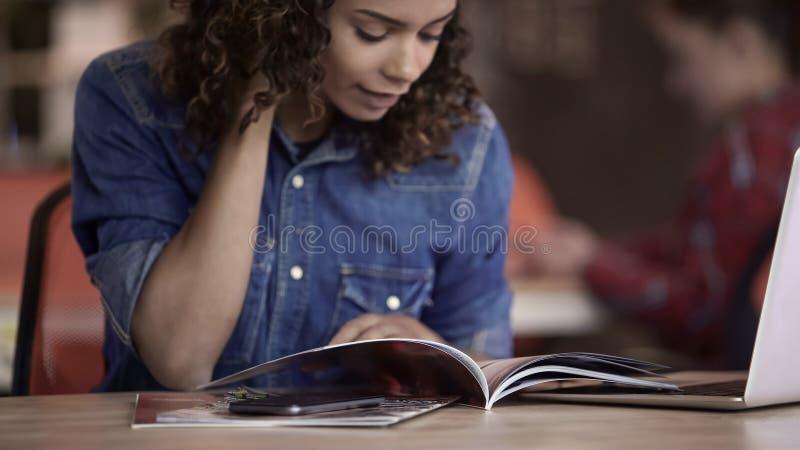 Курчавая девушка смешанной гонки смотря через фото в туристском журнале, планируя отключении стоковые изображения rf