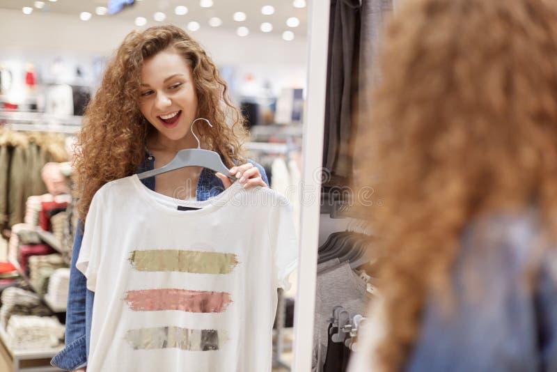 Курчавая девушка с широкой улыбкой выбирает футболку перед большим зеркалом магазина Эти одежды белые с нашивками в середине 3 стоковое фото