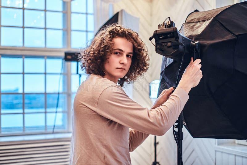 Курчавый красивый фотограф в студии которая смотрит в камеру стоковое изображение rf
