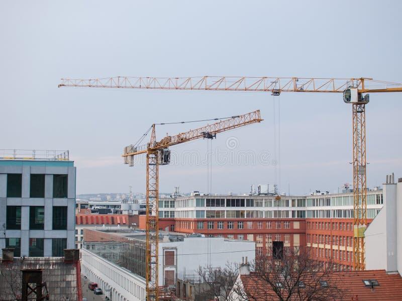 2 крана конструкции в городе окруженном современными зданиями стоковые фото