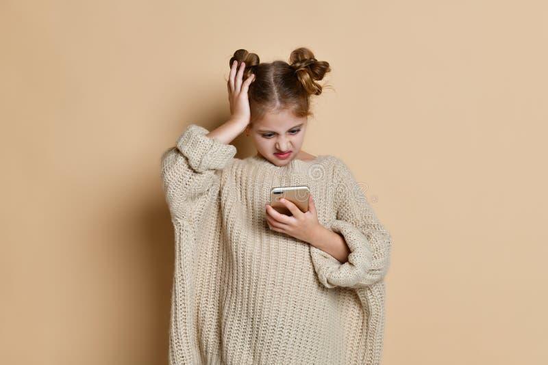 Красивая белокурая маленькая девочка смотрит телефон confusedly, фото студии на предпосылке стоковое фото rf