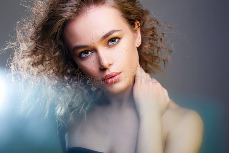 Красивая женщина в светах цвета изумляя курчавая девушка стоковая фотография