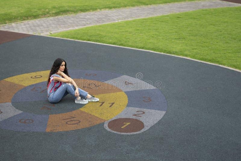 Красивая женщина на спортивной площадке смотрит прочь стоковая фотография