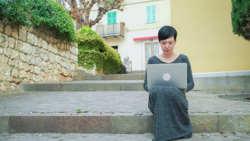 Красивая женщина сидя на лестницах используя компьютер перед домом цвета стоковое изображение rf