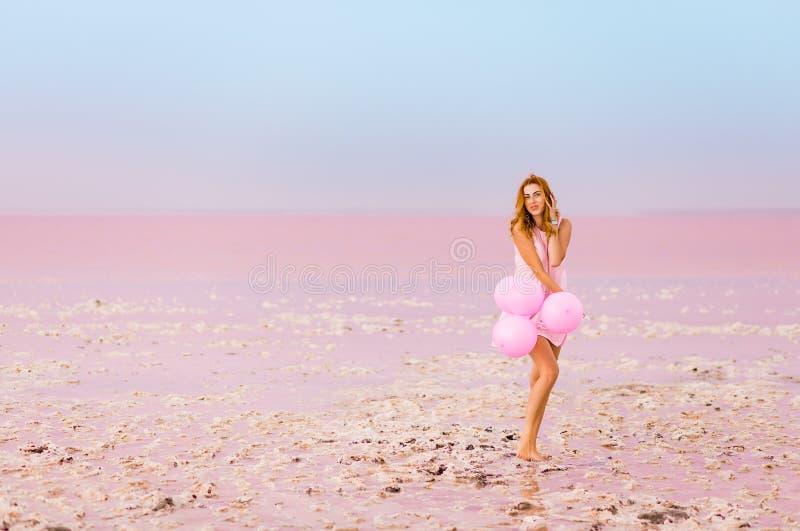 Красивая женщина с baloons на розовом озере соли стоковые фотографии rf