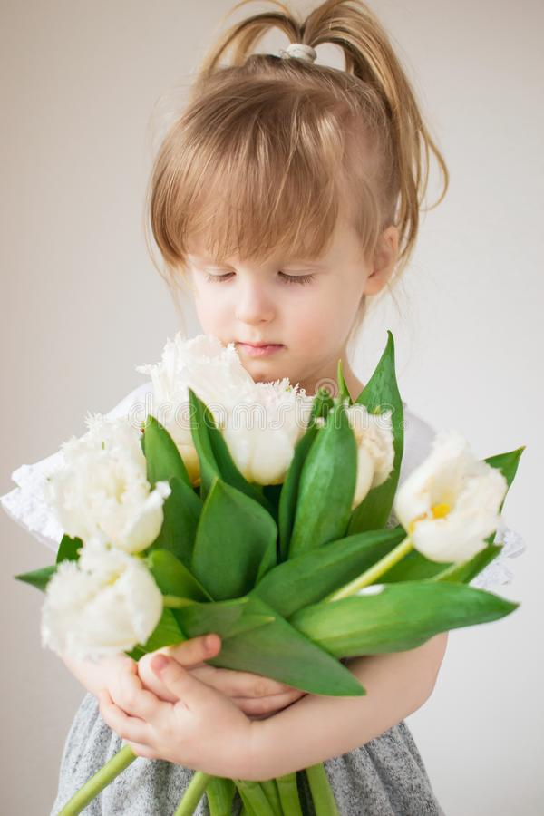 Красивая маленькая девочка держа букет цветков стоковые фотографии rf