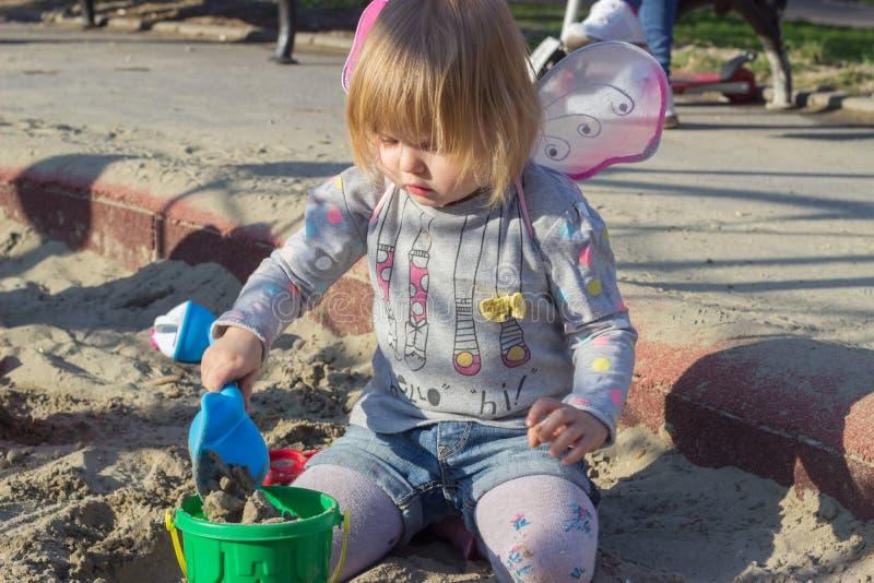 Красивая маленькая девочка с крыльями феи играя песок стоковая фотография rf