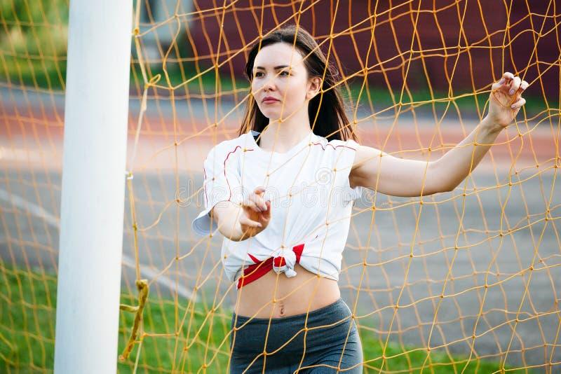 Красивая молодая атлетическая женщина в sportswear тренирует в стадионе на предпосылке цели футбола с футболом Она счастлива стоковая фотография rf