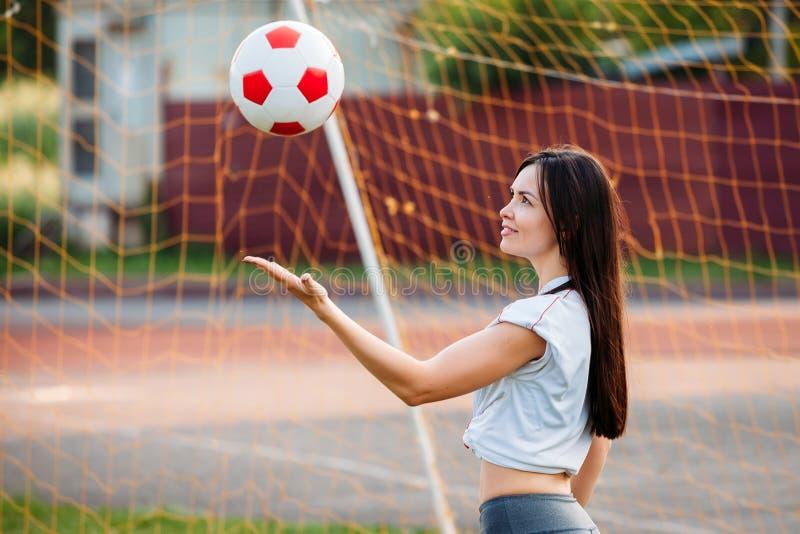 Красивая молодая атлетическая женщина в sportswear тренирует в стадионе на предпосылке цели футбола с футболом Она стоковое изображение