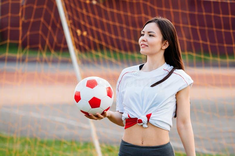 Красивая молодая атлетическая женщина в sportswear тренирует в стадионе на предпосылке цели футбола с футболом Она стоковая фотография