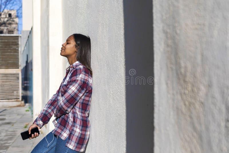 Красивая молодая Афро-американская женщина полагаясь на белой стене outdoors в улице пока держащ телефон и слушая музыку мимо стоковые изображения rf