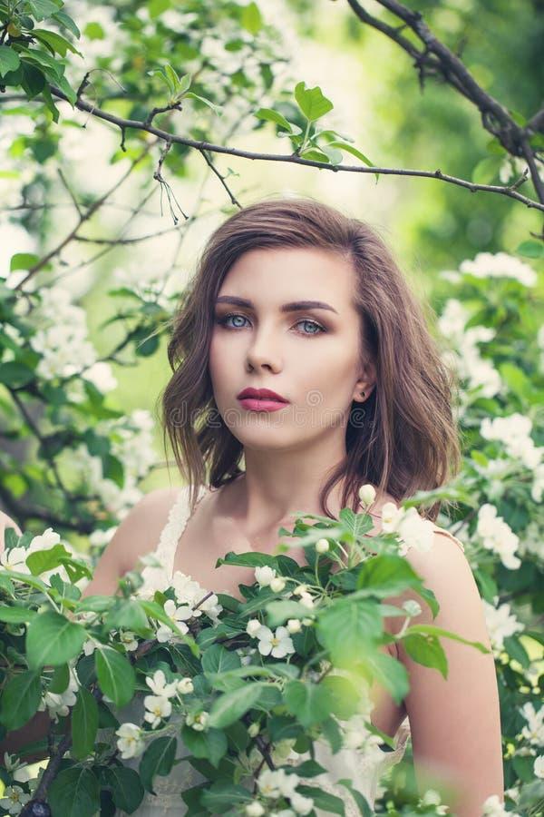 Красивая молодая женщина весны в белых цветках в зацветая саде стоковое фото rf