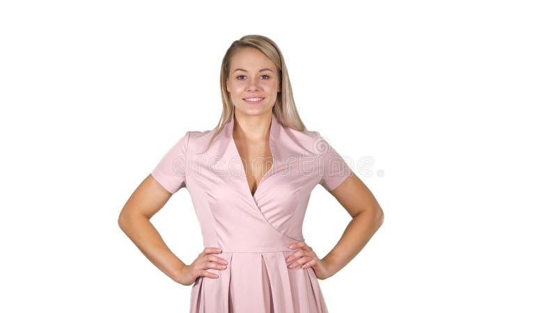 Красивая молодая женщина идя с руками на бедрах и говоря на белой предпосылке стоковое фото