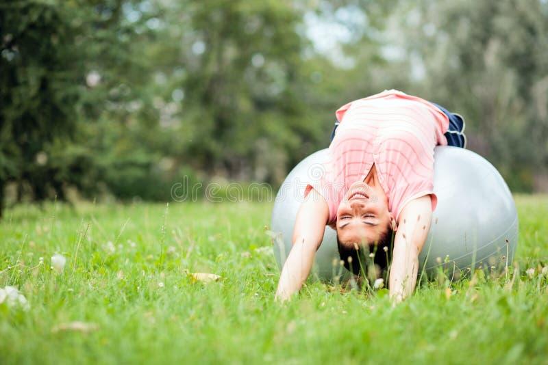 Красивая молодая женщина лежа на ей назад на шарике фитнеса и протягивая в парке стоковая фотография rf