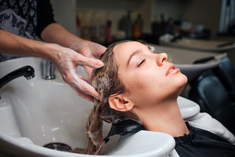 Красивая молодая женщина сидя около раковины пока парикмахер моя ее волосы в салоне красоты Парикмахер на работе стоковое изображение