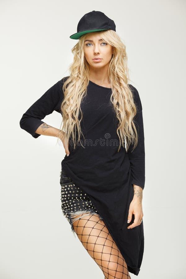 Красивая молодая женщина с белокурыми длинными волосами в стильном взгляде swag на белой изолированной предпосылке крышка, длинна стоковое фото