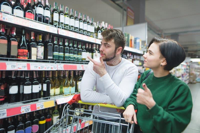 Красивая молодая пара выбирает вино в отделе алкоголя супермаркета Покупки семьи в магазине стоковые изображения