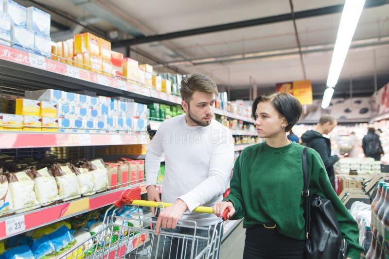 Красивая молодая пара идя в супермаркет с тележкой и говорить Выбор семьи продуктов супермаркета стоковая фотография rf