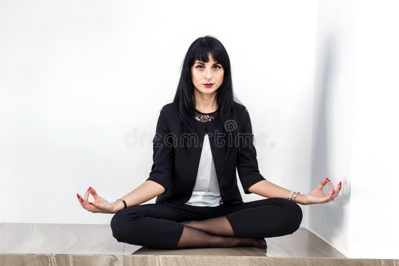 Красивая молодая серьезная женщина одетая в черном деловом костюме сидя в положении лотоса на поле в офисе, смотря к камере стоковые изображения rf