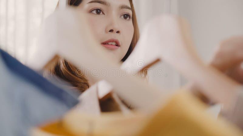 Красивая привлекательная молодая азиатская женщина выбирая ее одежды обмундирования моды в шкафе дома или магазине Девушка думает стоковые фотографии rf