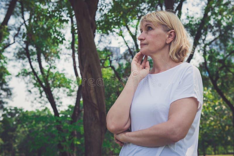 Красивая пожилая женщина думая в парке стоковое изображение