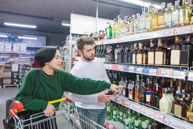 Красивая положительная пара выбирает вино в супермаркете Молодая семья покупает алкоголь стоковое изображение rf
