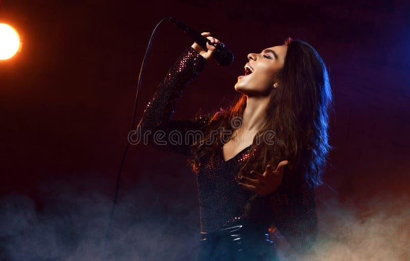 Красивая поя девушка курчавые афро волосы Певица женщины красоты поет с песней караоке микрофона на дыме этапа, фарах стоковая фотография