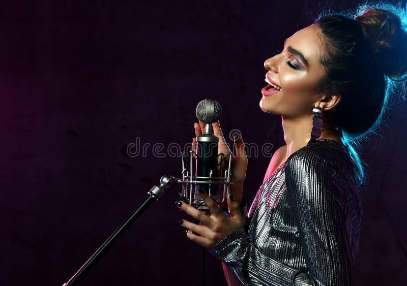 Красивая поя девушка курчавые афро волосы Певица женщины красоты поет с песней караоке микрофона на дыме этапа, фарах стоковое фото rf