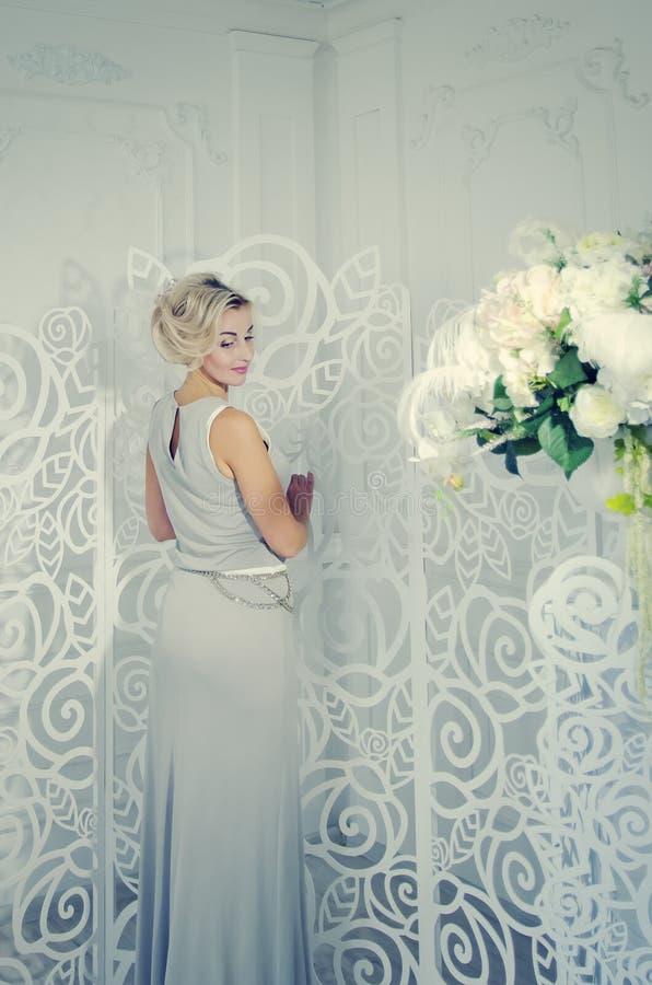 Красивая дама в длинном выравниваясь платье стоит в светлой комнате с красивым интерьером Тонизировать в стиле instagram стоковое фото