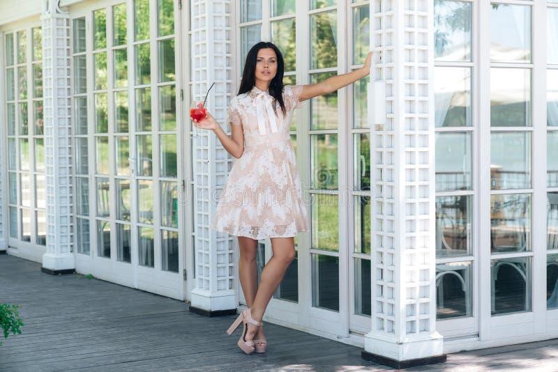 Красивая девушка брюнета со стеклом лимонада представляя в бежевом платье цвета вне кафа около деревянной и стеклянной стены стоковое изображение