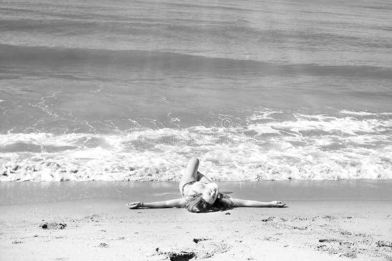 Красивая девушка в бикини представляя на дезертированном пляже белый песок, море бирюзы и маленькая девочка стоковые фото