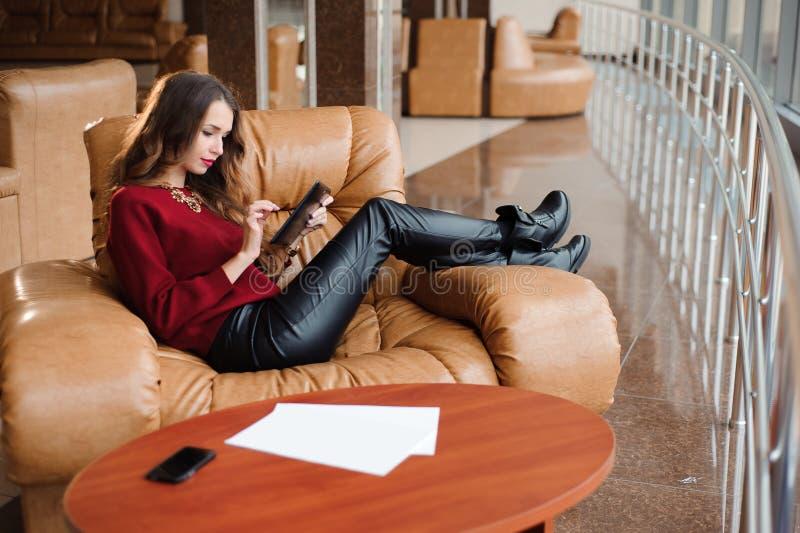 Красивая девушка в гостиной аэропорта на софе стоковая фотография