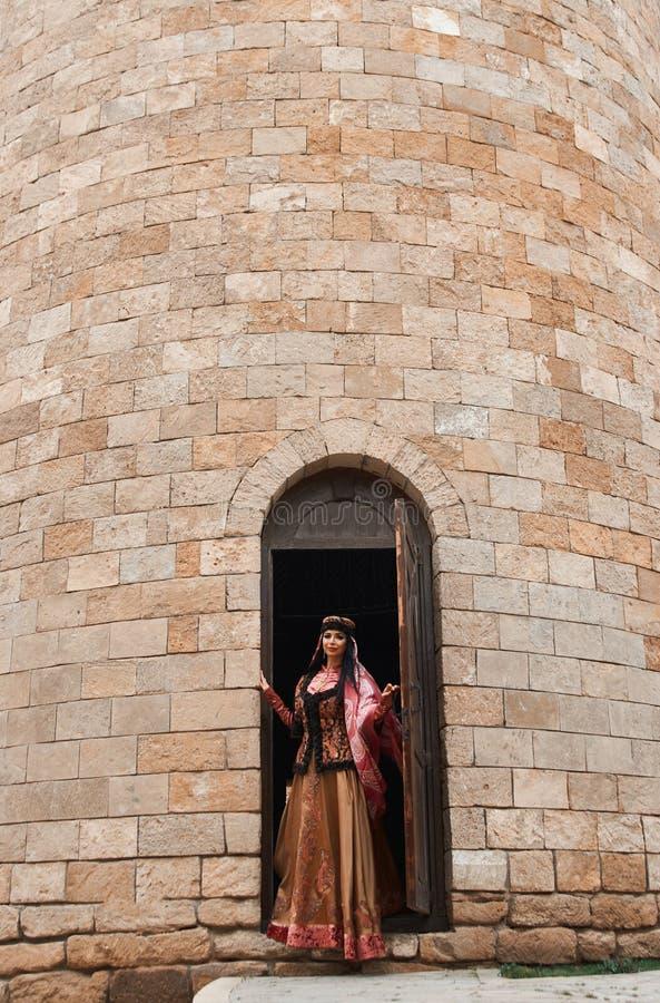 Красивая девушка в традиционном платье приходит из двери дома кирпича стоковые изображения rf