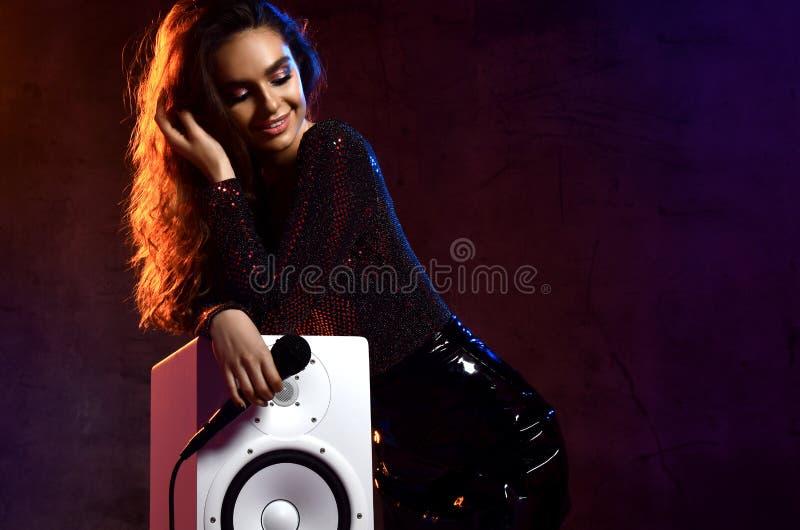 Красивая девушка певицы с курчавыми афро волосами спеть с песней караоке микрофона около аудио диктора акустической коробки удале стоковое изображение rf