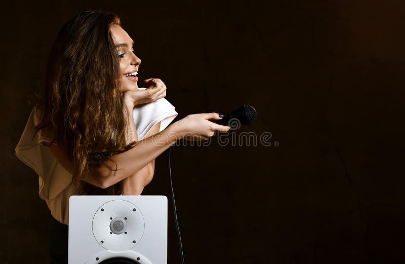 Красивая девушка певицы с курчавыми афро волосами спеть с песней караоке микрофона около аудио диктора акустической коробки удале стоковые изображения rf