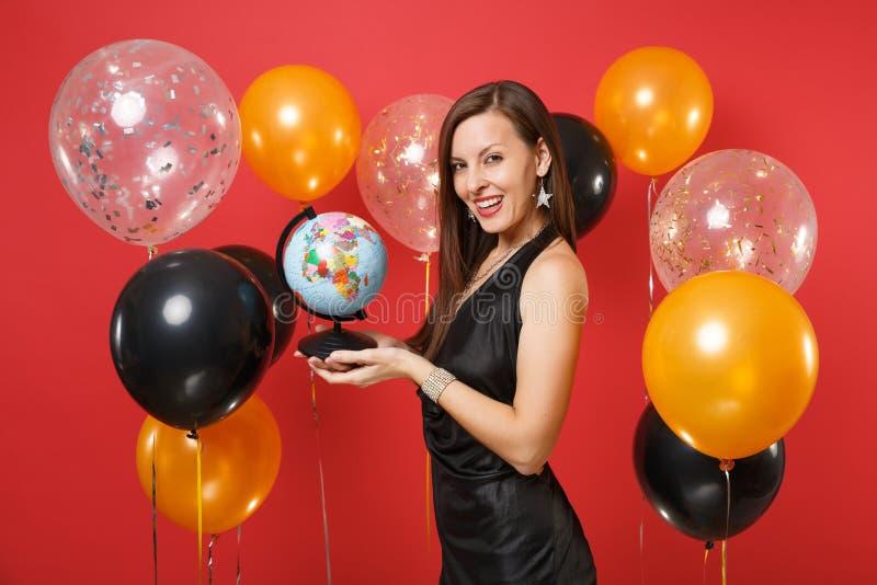 Красивая усмехаясь молодая женщина в меньший черный праздновать платья, держа глобус мира на ярком красном воздухе предпосылки стоковые фото