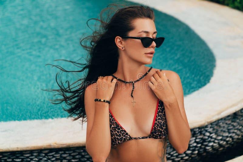 Красивая чувственная девушка брюнета в солнечных очках и купальнике представляя около бассейна стоковая фотография