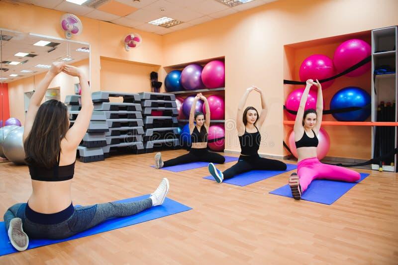 Красивые женщины делая фитнес или pilates работают и протягивать стоковое изображение rf