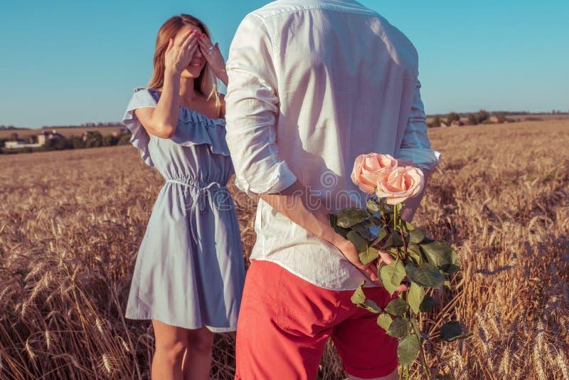 Красивые и молодые человек и женщина пар, летом в пшеничном поле, за подарком букет цветков, сюрприз и стоковое изображение rf