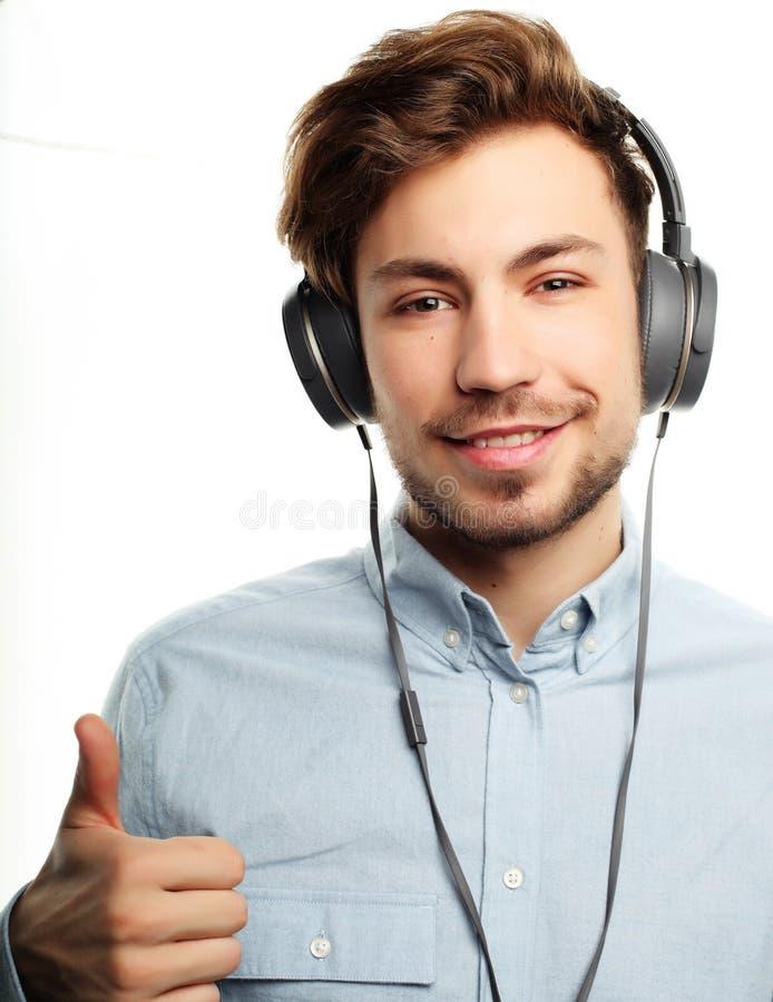 Красивые наушники молодого человека нося и слушать к музыке стоковое фото
