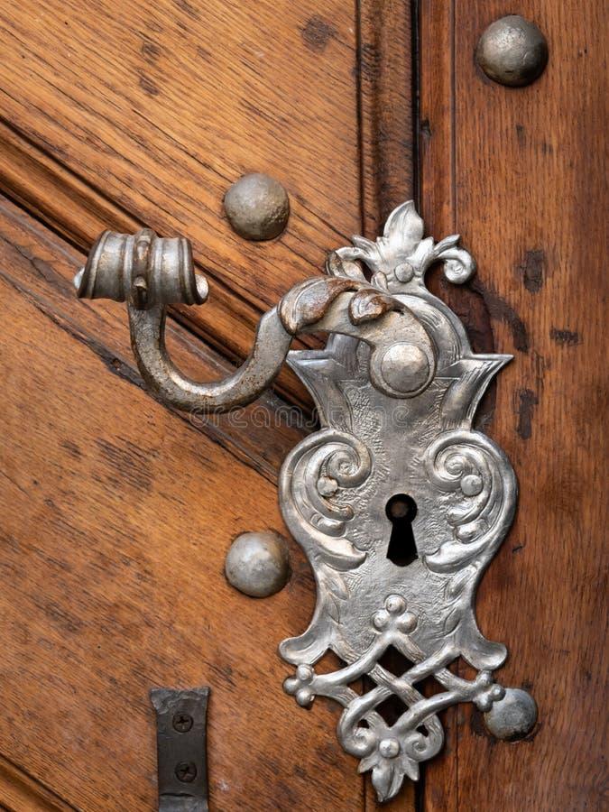 Красивые старые дверная ручка и украшение сделали из серебра на коричневой двери стоковая фотография rf