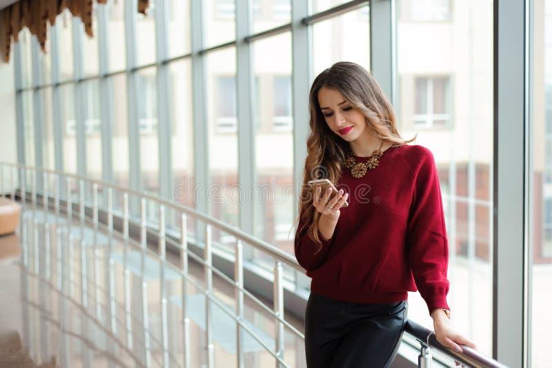 Красивые sms сочинительства бизнес-леди на мобильном телефоне стоковая фотография